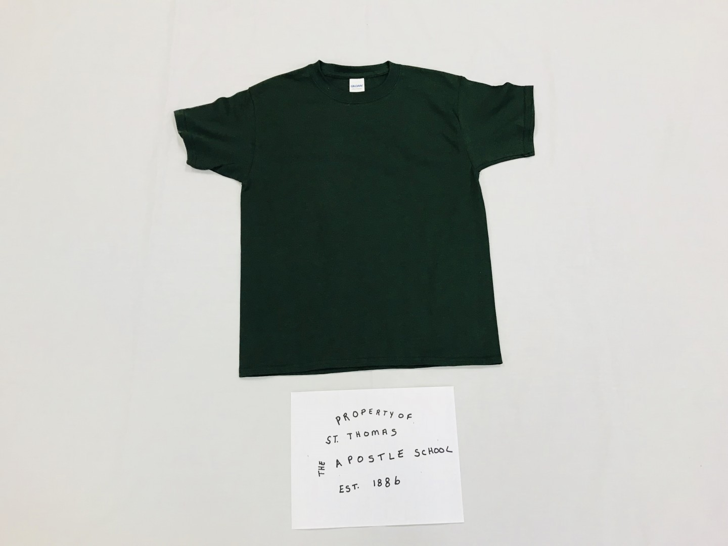 Solid forest green t-shirt with Property of St. Thomas the Apostle School logo