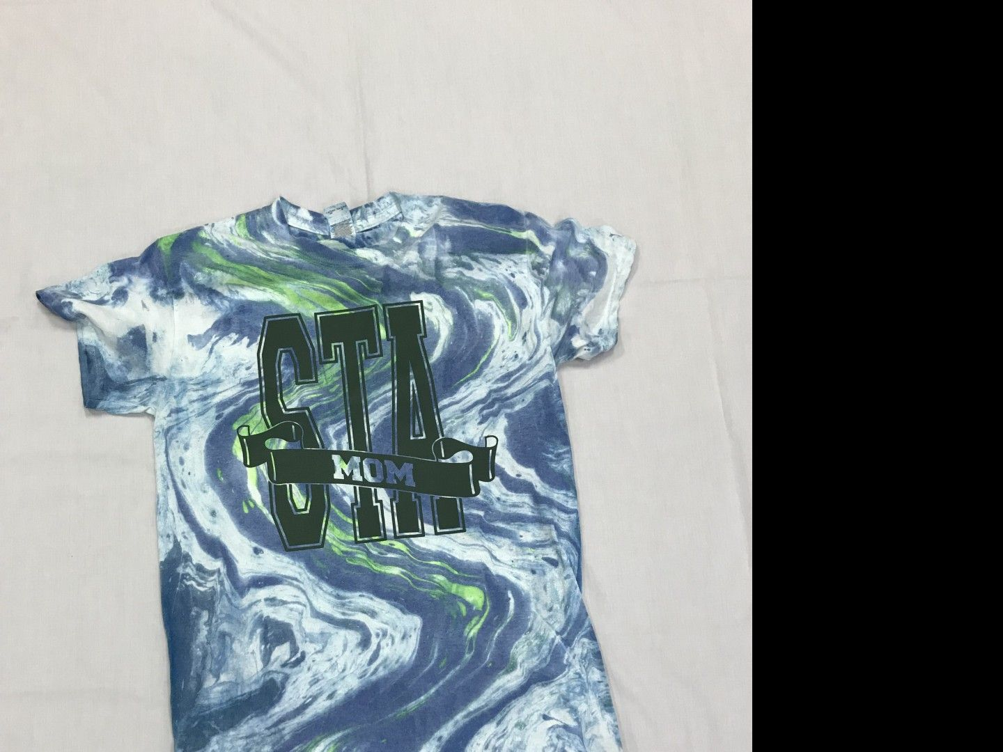 Tie dyed multi color t-shirt with either STA MOM, STA DAD or STA GRANDPARENT dark green logo